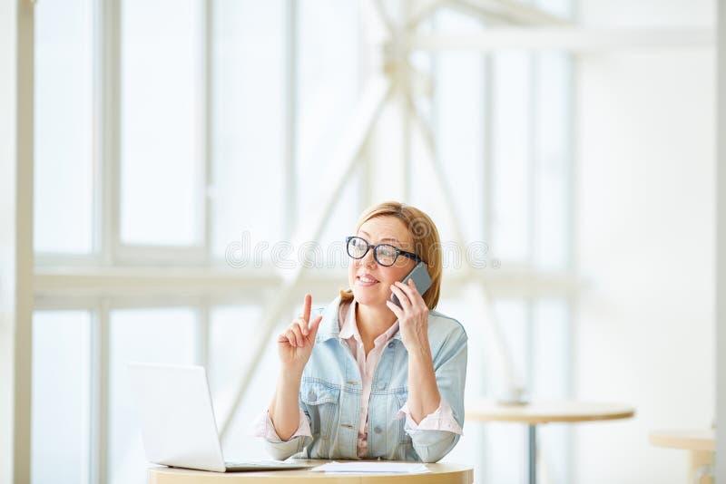 Erfolgreiche Geschäftsfrau, die am Telefon spricht stockbild