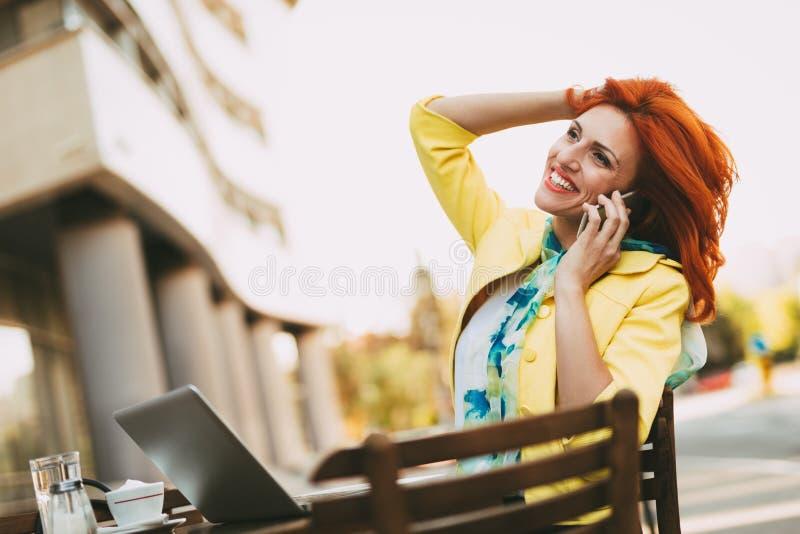 Erfolgreiche Geschäftsfrau On ein Bruch in einem Straßen-Café stockbild