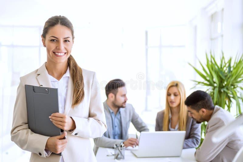 Erfolgreiche Geschäftsfrau im Büro, das eine Gruppe führt stockfotos
