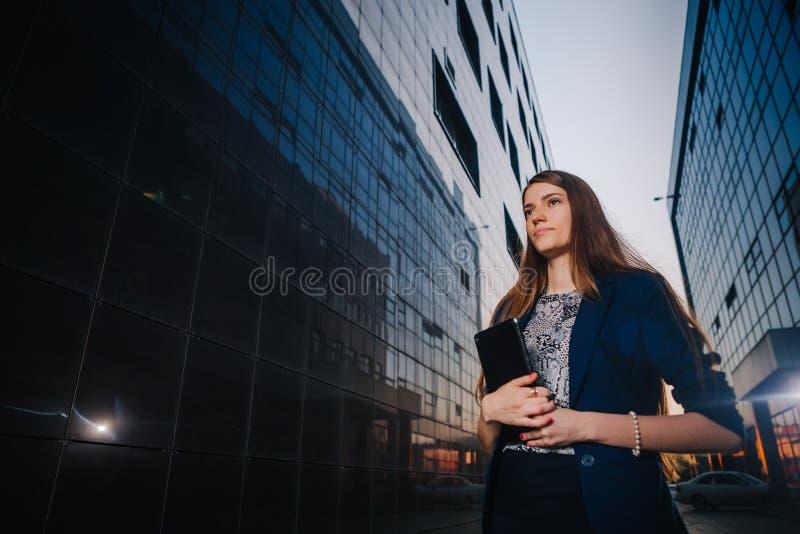 Erfolgreiche Geschäftsfrau steht auf dem Hintergrund von Gebäuden und Haltentablet-computer StadtGeschäftsfraufunktion lizenzfreies stockfoto