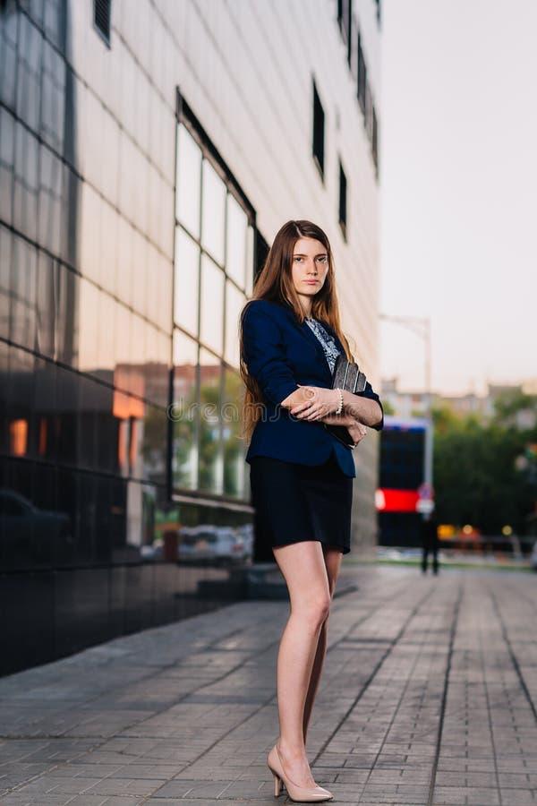 Erfolgreiche Geschäftsfrau steht auf dem Hintergrund von Gebäuden und Haltentablet-computer StadtGeschäftsfraufunktion stockbilder