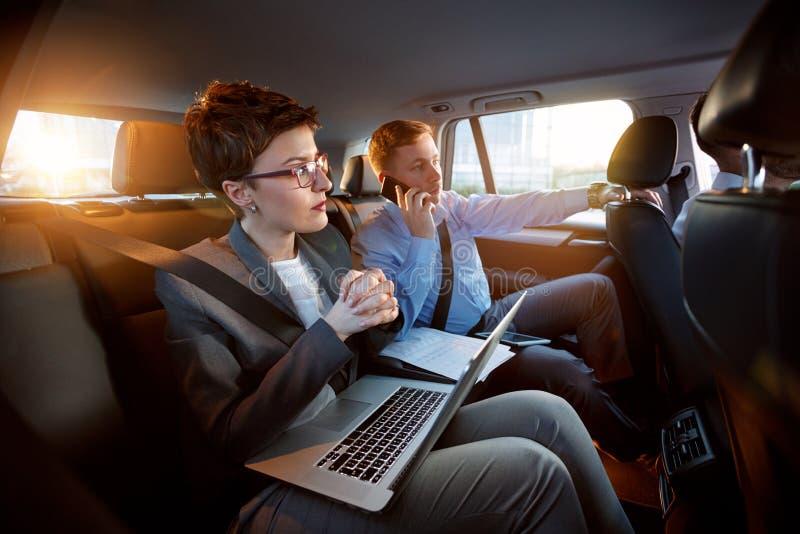Erfolgreiche Geschäftsleute, die im Rücksitz des Autos zusammenarbeiten lizenzfreie stockfotos
