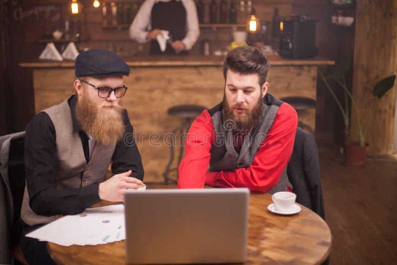 Erfolgreiche Gesch?ftsm?nner, die eine Sitzung ?ber Finanzen und Industrie in einer Kaffeestube haben lizenzfreie stockfotografie