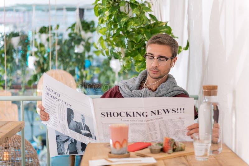 Erfolgreiche Geschäftsmannlesemorgennachrichten, die in der Cafeteria frühstücken lizenzfreies stockbild