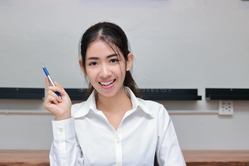 Erfolgreiche junge asiatische Geschäftsfrau mit dem Stift, der Idee an Arbeitsplatz hat stockfotografie