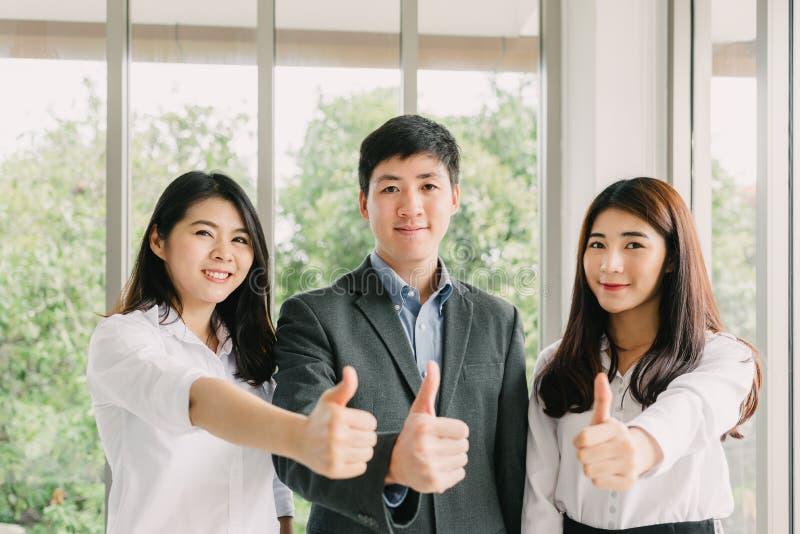 Erfolgreiche junge asiatische Geschäftsleute, die sich Daumen zeigen lizenzfreie stockfotos