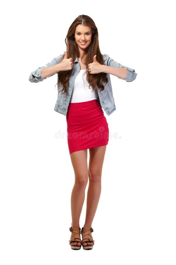 Erfolgreiche junge Frau mit den Daumen oben im Studio stockfotos
