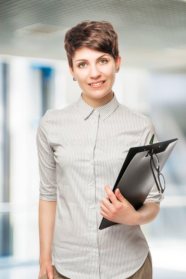 Erfolgreiche junge Frau mit einem Ordner stockfotografie