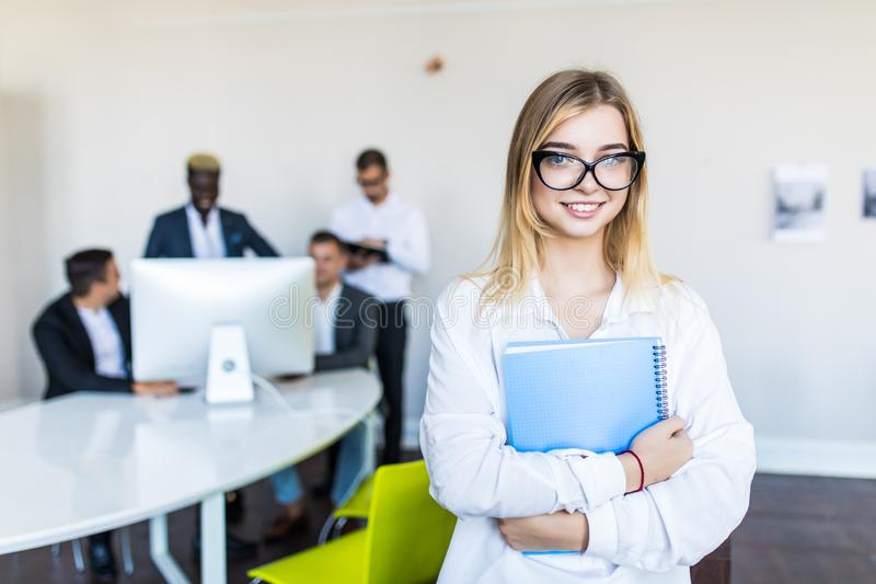 Erfolgreiche junge Geschäftsfrau in den Gläsern, die vor multi Ethnie Leuten im Büro stehen stockbild