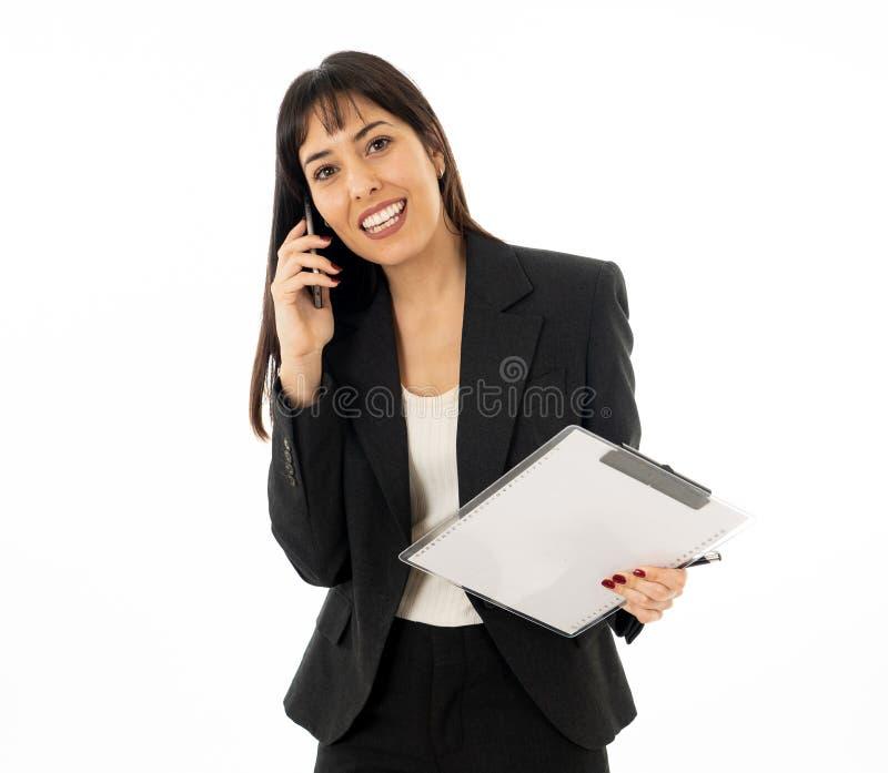 Erfolgreiche junge Geschäftsfrau, die am Telefon hält einen Ordner spricht Getrennt auf weißem Hintergrund lizenzfreie stockfotografie