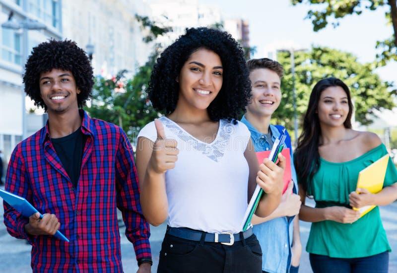 Erfolgreiche lateinamerikanische Studentin mit Gruppe internationalen Studenten lizenzfreie stockfotografie