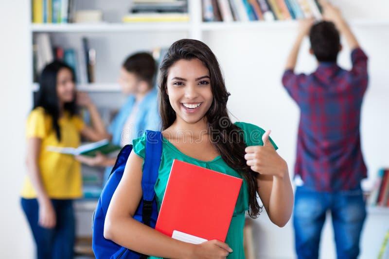 Erfolgreiche lateinamerikanische Studentin mit Gruppe Studenten lizenzfreie stockfotografie