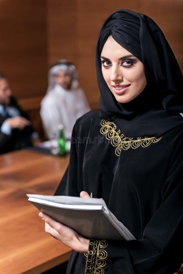 Erfolgreiche moslemische Frau, die ein schwarzes hijab trägt stockfotos