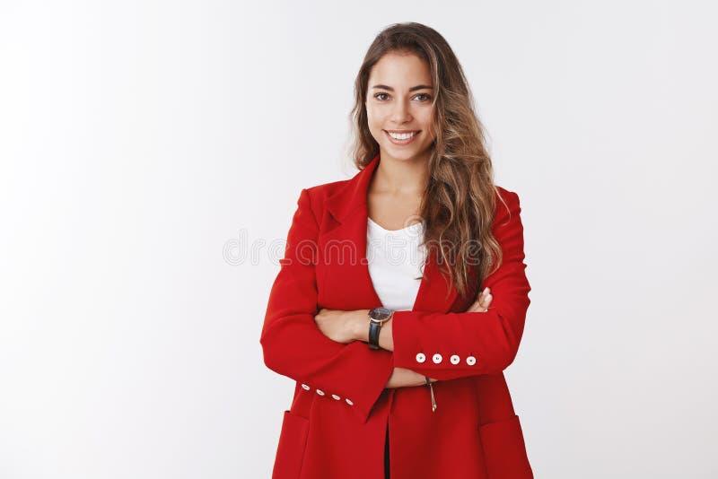 Erfolgreiche sch?ne Gesch?ftsfrau, welche die Querarme der roten Jacke ?berzeugt, l?chelndes selbstsicheres anspruchsvolles, wiss lizenzfreie stockfotos