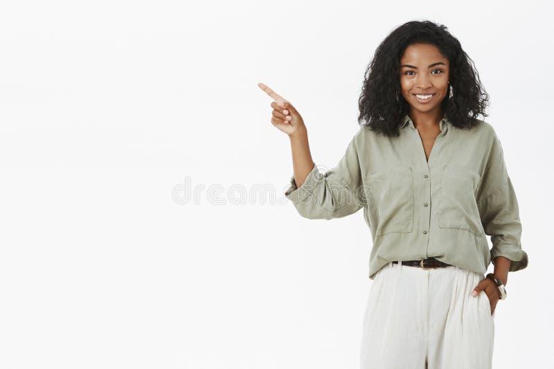 Erfolgreiche stilvolle und glückliche dunkelhäutige Geschäftsfrau, die Projekt nahe Mangoldgemüseholdinghand beim Taschenzeigen d lizenzfreie stockfotografie