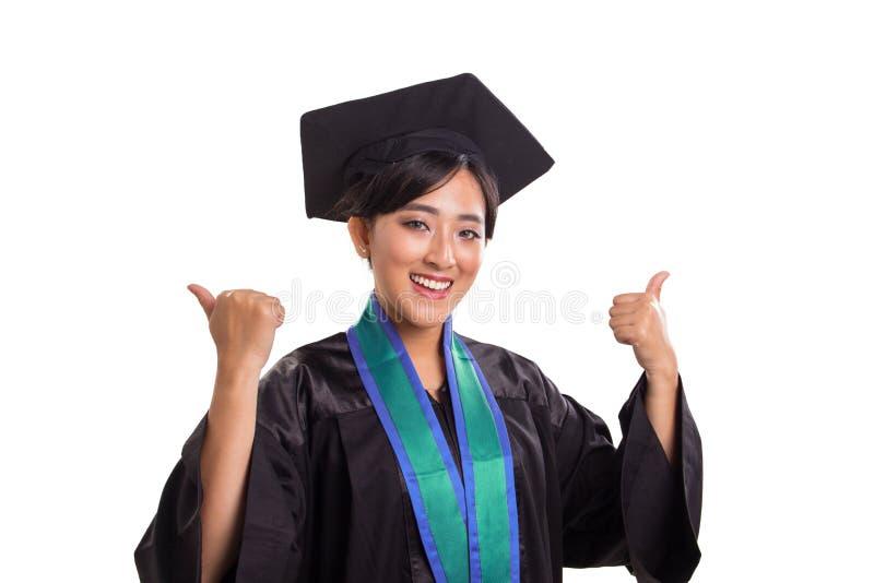 Erfolgreiche weibliche Daumen des Absolvent zwei herauf das Porträt lokalisiert auf weißem Hintergrund lizenzfreie stockfotografie