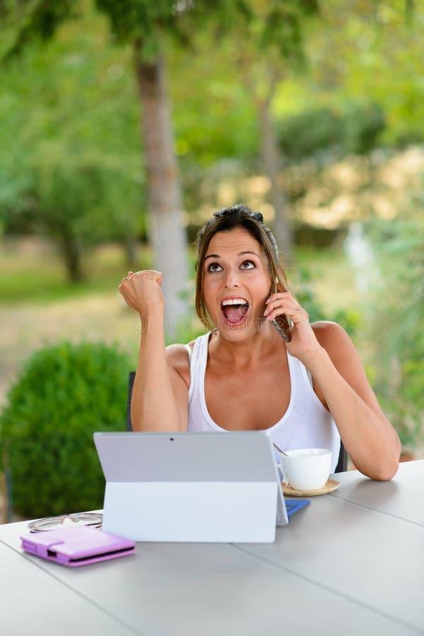 Erfolgreiche zufällige Frau mit Laptop draußen stockfotos