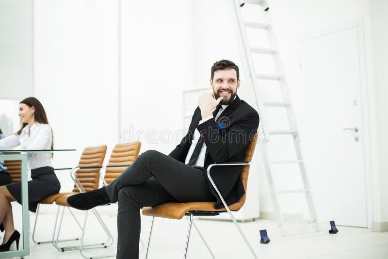 Erfolgreicher Angestellter der Firma sitzt auf einem Stuhl nahe dem Arbeitsplatz im Büro lizenzfreie stockfotografie