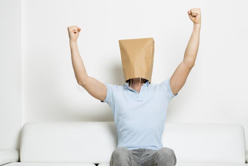 Erfolgreicher anonymer Mann mit dem Kopf umfasst und den Armen in der Luft. lizenzfreie stockfotografie