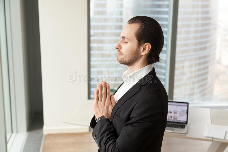 Erfolgreicher Geschäftsmann, der am Arbeitsplatz im modernen Büro meditiert stockfoto