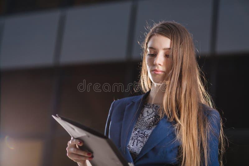 Erfolgreicher Geschäftsmann, der auf den Hintergrundgebäuden betrachten die Ordnerdiagramme von Verkäufen steht StadtGeschäftsfra lizenzfreies stockfoto