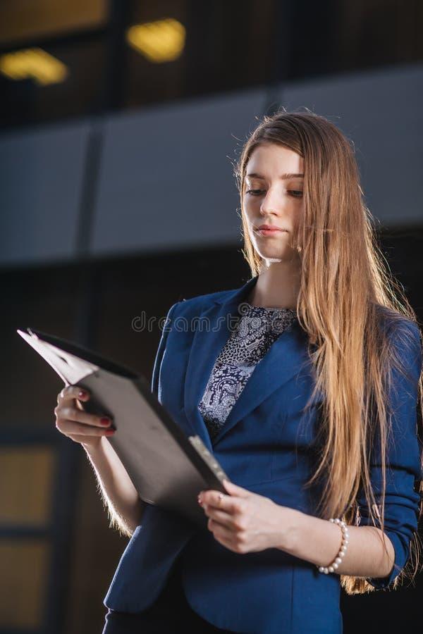 Erfolgreicher Geschäftsmann, der auf den Hintergrundgebäuden betrachten die Ordnerdiagramme von Verkäufen steht StadtGeschäftsfra lizenzfreie stockfotografie