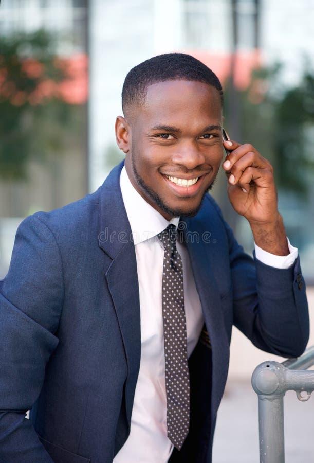 Erfolgreicher Geschäftsmann, der durch Handy nennt stockfotos