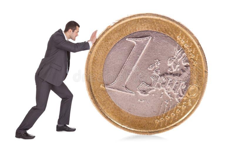 Erfolgreicher Geschäftsmann, der eine Euromünze drückt stockfoto