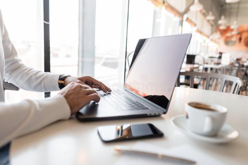 Erfolgreicher Geschäftsmann, der hinter einem Laptop in einem Café arbeitet Bloggermann hält sein persönliches Blog auf einem Lap lizenzfreie stockfotografie