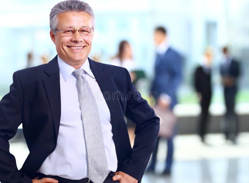 Erfolgreicher Geschäftsmann, der mit seinem Personal im Hintergrund im Büro steht stockbild