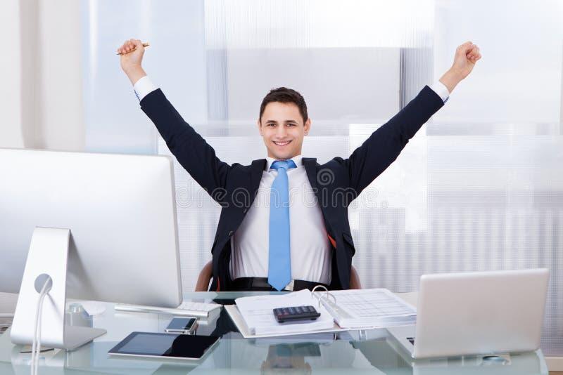 Erfolgreicher Geschäftsmann, der am Schreibtisch sitzt stockfoto