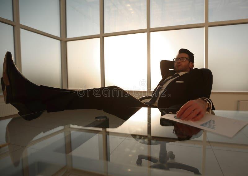 Erfolgreicher Geschäftsmann, der am Tisch sich entspannt stockbild