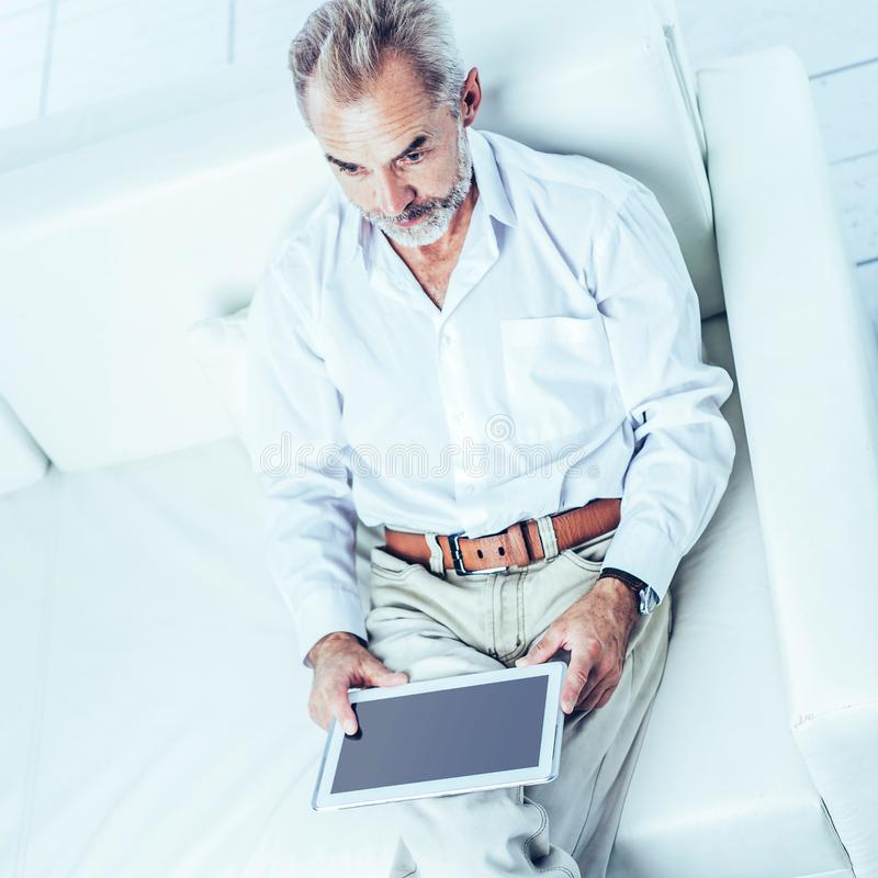Erfolgreicher Geschäftsmann mit der digitalen Tablette, die in modernem von sitzt lizenzfreies stockbild