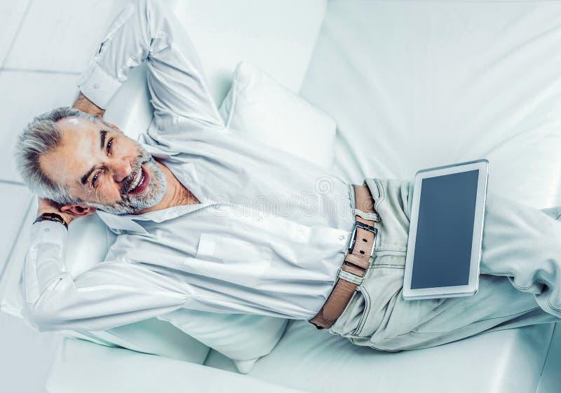 Erfolgreicher Geschäftsmann mit der digitalen Tablette, die weg in modernem sitzt lizenzfreie stockfotos