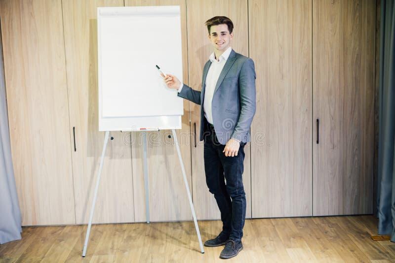 Erfolgreicher Geschäftsmann mit einer Flip-Chart in einer Darstellung im modernen Büro lizenzfreies stockbild