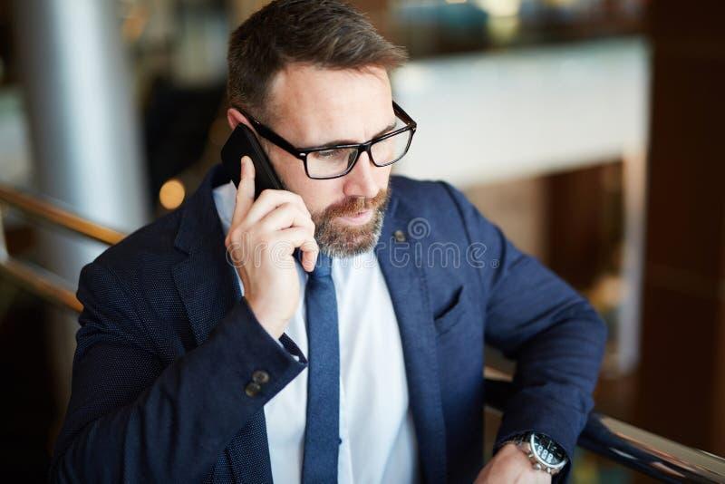 Erfolgreicher Geschäftsmann am Telefon mit Partner lizenzfreies stockbild