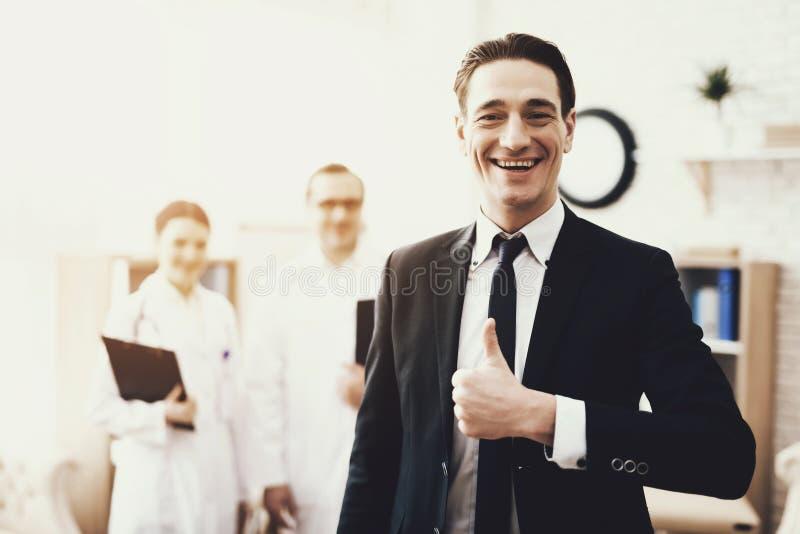 Erfolgreicher Geschäftsmann zeigt sich Daumen während in der Klinik Unscharfe Doktoren im Hintergrund stockfotografie
