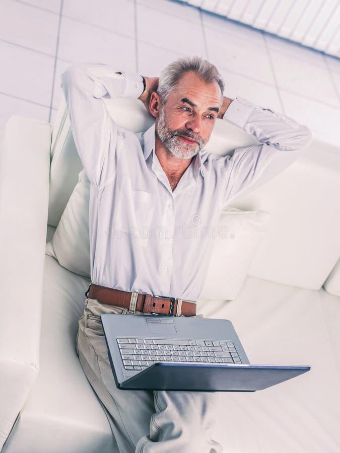 Erfolgreicher Gesch?ftsmann, der an dem Laptop sitzt auf Sofa im modernen B?ro arbeitet stockfotos