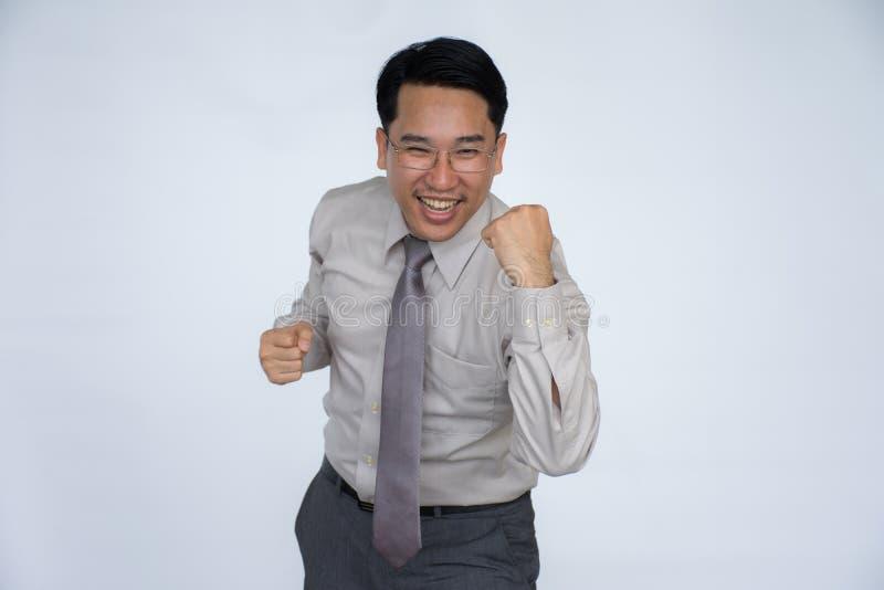 Erfolgreicher glücklicher Geschäftsmann, der mit seinen geballten Fäusten zujubelt lizenzfreie stockfotos