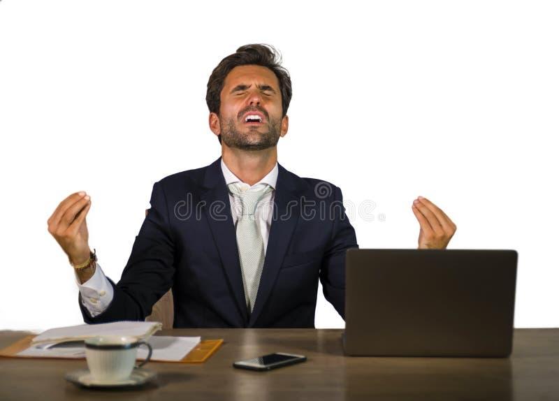 Erfolgreicher hübscher Geschäftsmann in der Klage, die am Bürocomputertisch Geld des Finanzerfolgs feiernd gewinnendes lächelndes stockfotografie