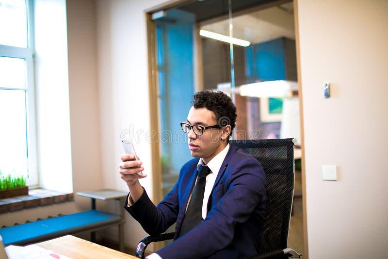 Erfolgreicher männlicher Jurist, der online auf Mobiltelefon plaudert Manager unter Verwendung der Apps am Zelltelefon stockfotografie