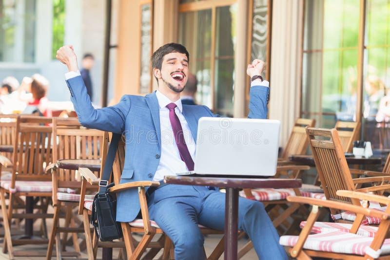 Erfolgreicher Mann übergibt herauf im Freien am Café stockfoto