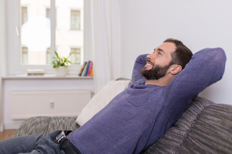 Erfolgreicher Mann, der sich zu Hause auf dem Sofa entspannt stockbilder