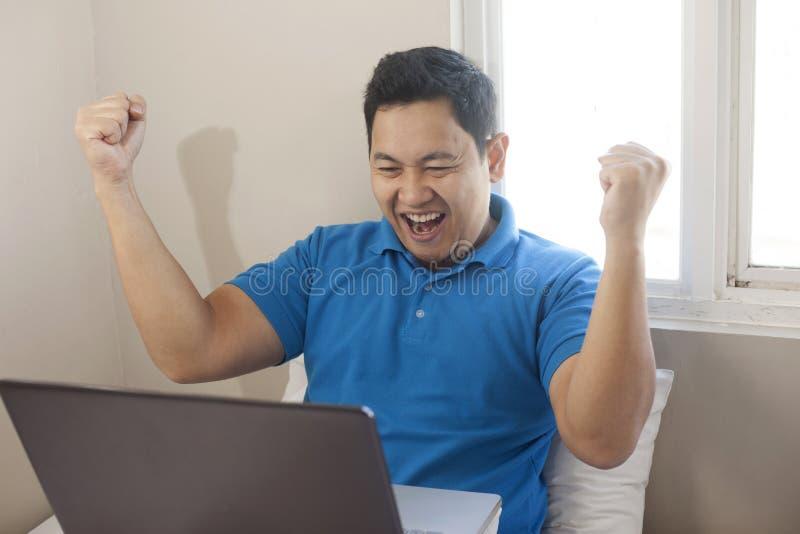 Erfolgreicher Mann, der Sieg, Unternehmer Working Online Business vom Haus feiert lizenzfreies stockfoto