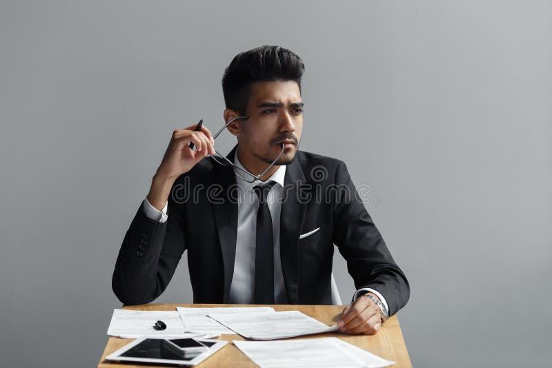 Erfolgreicher Mann mit den Gläsern, die auf dem Tisch weg von der Kamera, der Tablette, Telefon und Papieren schauen lizenzfreies stockbild