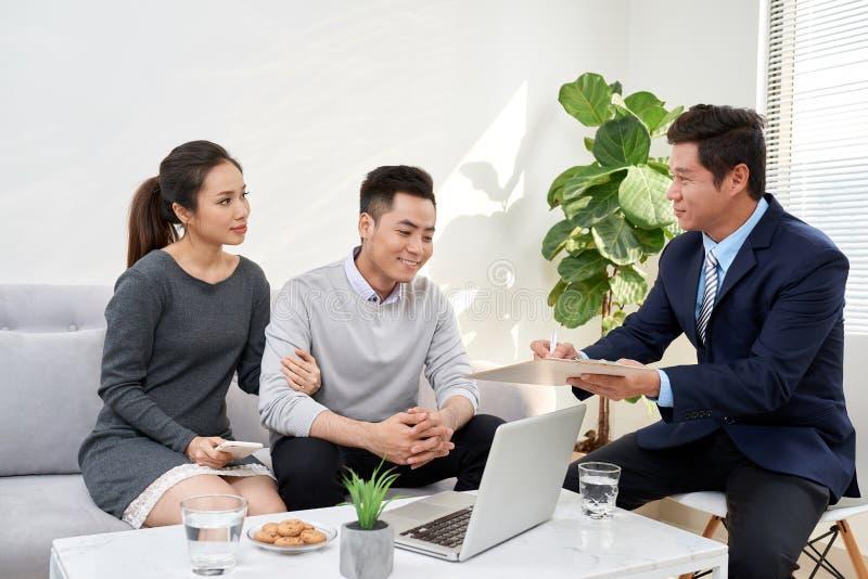 Erfolgreicher Rechtsanwalt, der Beratung zu den Familienpaaren über kaufendes Haus gibt lizenzfreies stockbild