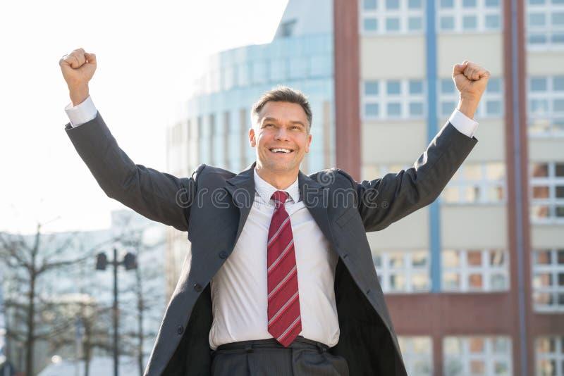 Erfolgreicher reifer aufgeregter Geschäftsmann With Arm Raised stockbilder