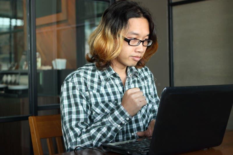 Erfolgreicher und überzeugter junger asiatischer Hippie mit der zufälligen Kleidung, die mit Laptop für seinen Job an Arbeitsplat stockfotos