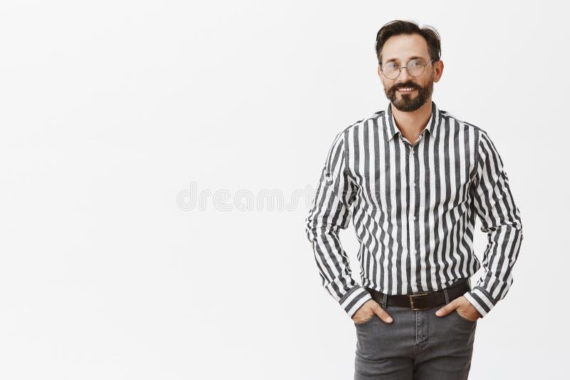 Erfolgreicher und überzeugter männlicher Unternehmer im stilvollen Ausstattungs- und Glashändchenhalten, in den Taschen und froh  stockfotografie