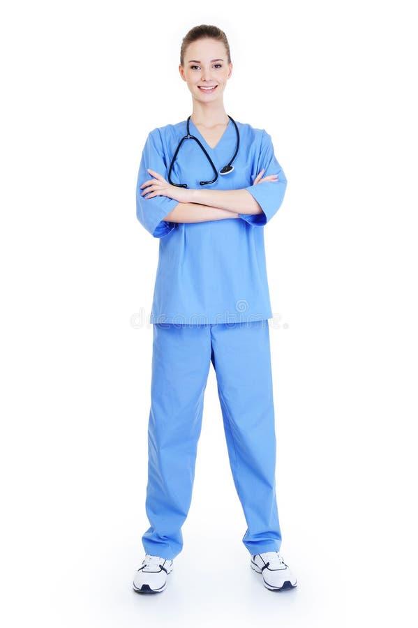 Erfolgreicher weiblicher Chirurg, der in der blauen Uniform steht lizenzfreies stockbild